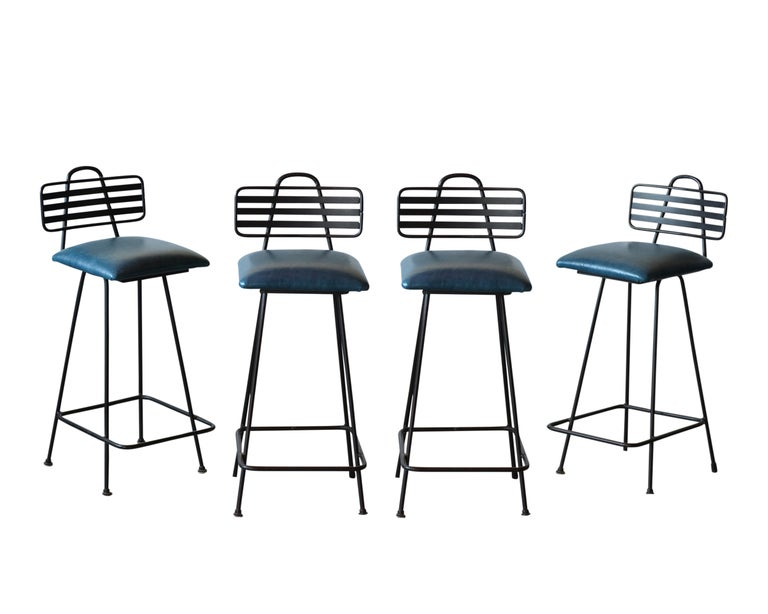 These Four Mid-Century Leather Bar Stools are made out of wrought-iron, feature a Harpin backrest design, and rest on stretched legs frame newly painted in black color. The seats have all been upholstery in blue color leather with new comfortable