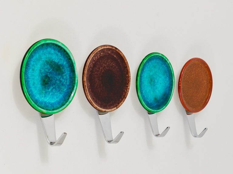A set of four colorful wall hooks, executed in Italy in the 1960s. Made of chrome-plated brass with colorful round enameled ceramic covers. In very good condition.