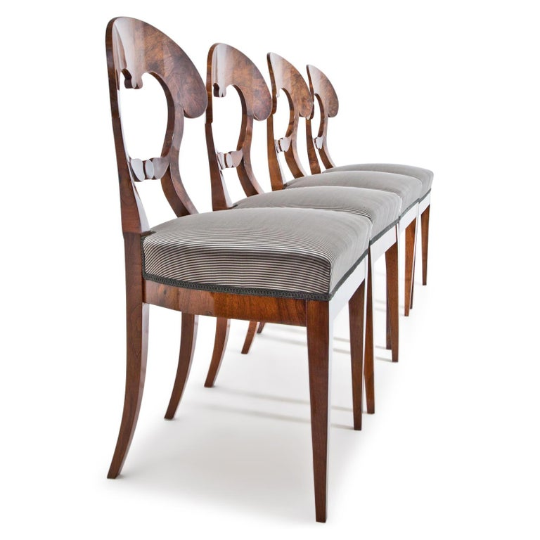 Four Biedermeier walnut armchairs with straight rails, standing on tapered feet. The rear legs are slightly curved. The shovel-shaped backrests with decorative strutting show Fine thread inlays. The chairs were professionally refurbished and