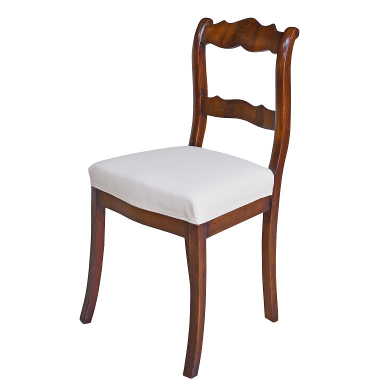 A beautiful set of four (4) North German Biedermeier dining chairs with solid mahogany frames with figured mahogany on the carved top & second rails, upholstered seat & saber legs. Lower Saxony, circa 1825. Original burlap forms on seats have been