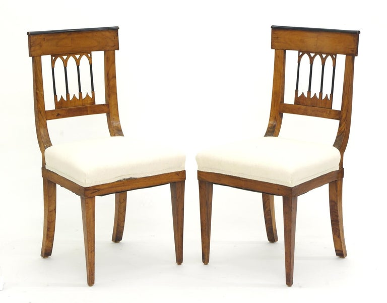 Set of four Biedermeier cherrywood side chairs, each with a tablet crest with Bookmatched veneers and ebonized molding over a Gothic splat; the upholstered seats on square tapering legs. Ideal for a breakfast room or card table.
