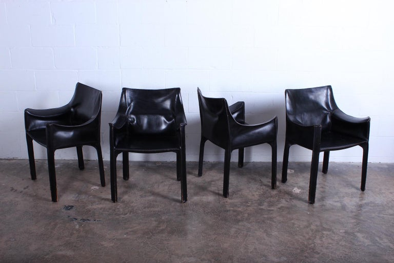 A vintage set of black leather cab armchairs with nice patina. Designed by Mario Bellini for Cassina.
