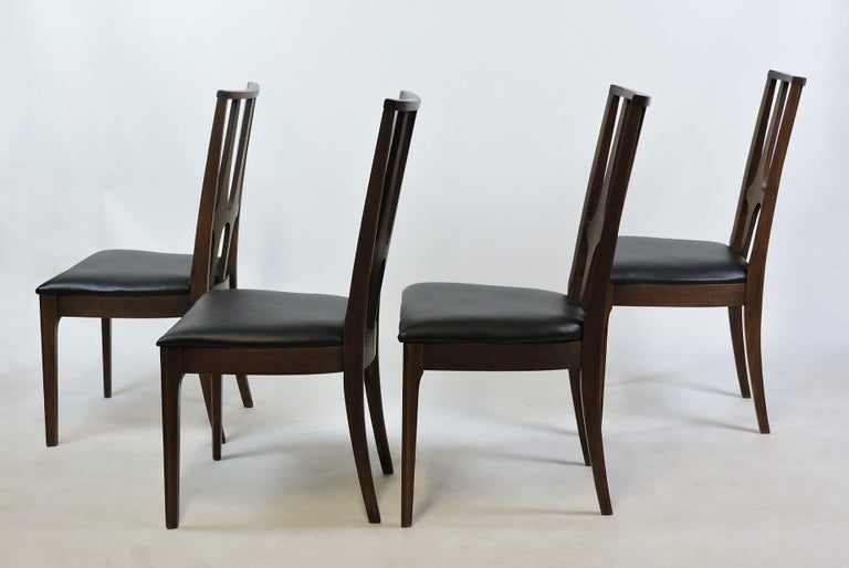 Handsome set of four Brasilia dining chairs manufactured by Broyhill. The Brasilia line was created by Broyhill in 1962 and was inspired by the esteemed Brazilian architect, Oscar Niemeyer. These chairs are made of walnut and have new black