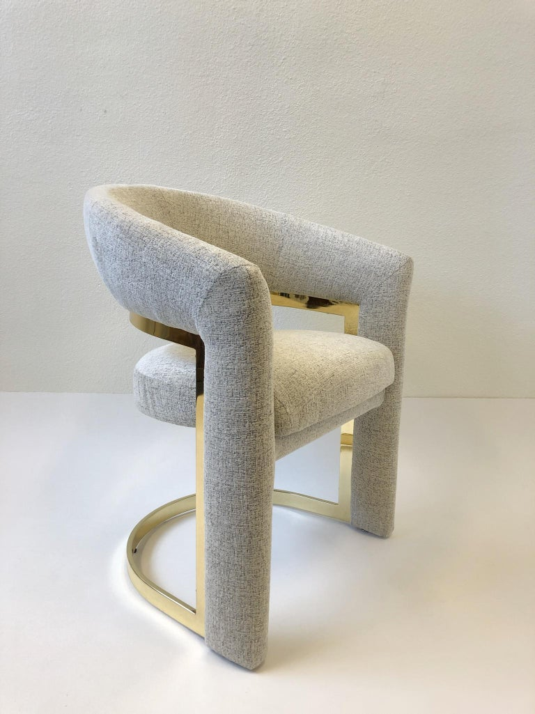 A set of four glamorous polish brass dining chairs designed in the 1980s by Design Institute of America. The chairs have been newly recovered in a soft off white with hints of light brown threads chenille tweed fabric. The brass is in original