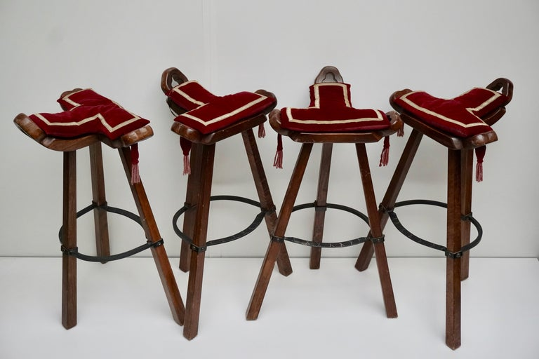 Set of four 'Brutalist' or 'Marbella' bar stools, in stained beech and metal, Spain, 1970s. A curved T-shape with three handles. The curved form makes sure the stool has a stabile seat, emphasized by the metal ring as footrest. These bar stools are