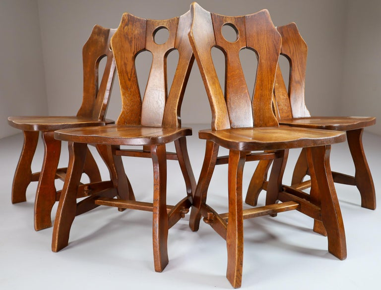 Set of four brutalist chairs in patinated oak, Belgium, 1960s.  A set of four wooden dining chairs. These chairs are made of oak and sculpturally crafted by hand. The craftsmanship is still visible, they are made of solid oak wood and constructed