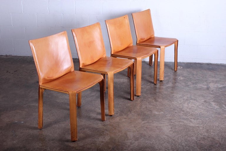 A set of four patinated leather cab chairs designed by Mario Bellini for Cassina.