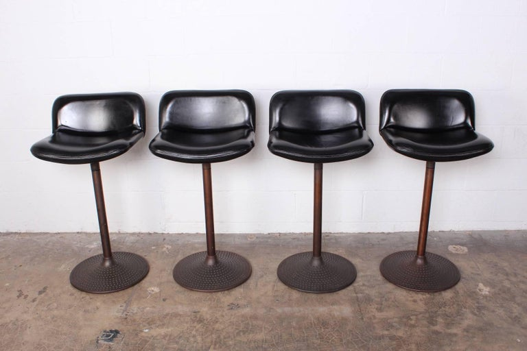A set of four bronze stools with original leather upholstery. Designed by Ilmari Tapiovaara.