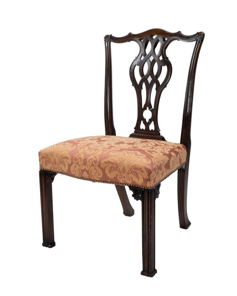 A set of four mahogany Chippendale style dining chairs with carved splats, stamped with the numbers for 1878