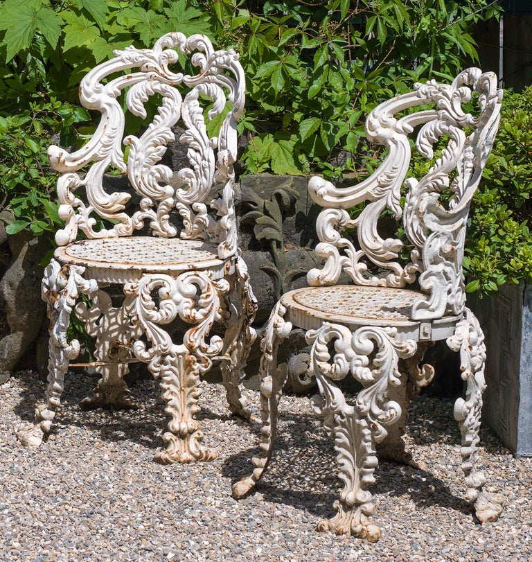A set of four highly ornate and elegant cast iron Victorian antique garden or conservatory chairs in the Rococo style with oval shaped acanthus scrolled backs, detatchable seats and quadruple splayed legs, English, circa 1850.