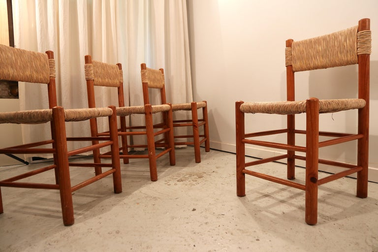 Wonderful set of 4 dining chairs by Charlotte Perriand, model Dordogne for Sentou. Pine wood structure in a wonderful condition and straw seat and back rest, in excellent condition as well. Another set of 4 is available, please ask in case