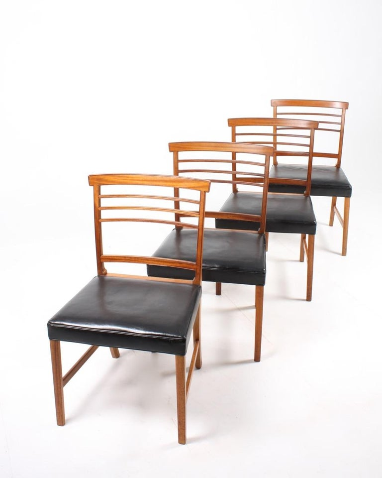 Set of four side chairs in mahogany with seats in black patinated leather. Designed by Ole Wanscher for A.J. Iversen cabinetmakers Denmark in the 1950s. Great original condition.