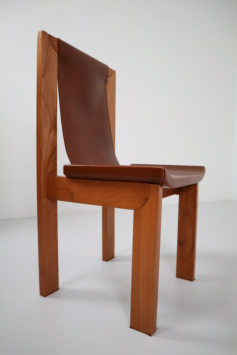 Set of four cognac leather dining chairs in elmwood, France 1960s . Cognac leather chairs from France, with a strong, architectural wooden frame. The leather seat is attached to frame on the sides and on the top. The cognac leather shows a very