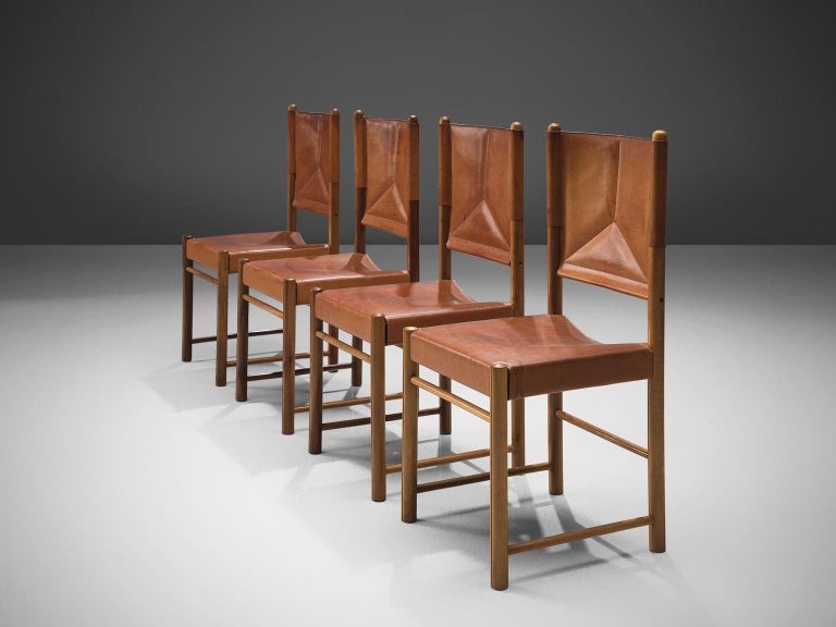 Set of four dining chairs, cognac leather, beech, Italy, circa 1960.  This set of four cognac leather dining chairs are stately and refined. The detailing and finish in this set of chairs is very high. The tripod stitched pattern on the back is