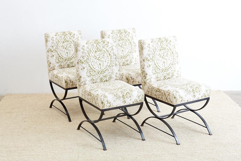 Stylish set of four wrought iron dining chairs featuring an x form curule style base. Heavy and solid made from bars of iron with round stretchers and square feet. Topped with a thick upholstered seat of organic linen fabric with a botanical style