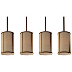 Set of Four 'Cylindre' Patinated Brass and Raffia Pendant Lights, Design Frères