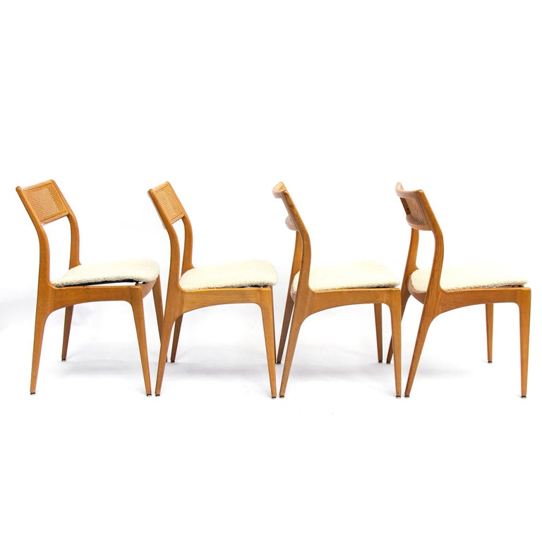 Set of four Danish midcentury oak dining chairs with a webbing back newly upholstered. The typical soft feminine shaped edges refer to the populair Danish hand of design. These chairs are special with the diagonal webbing back. Production date app