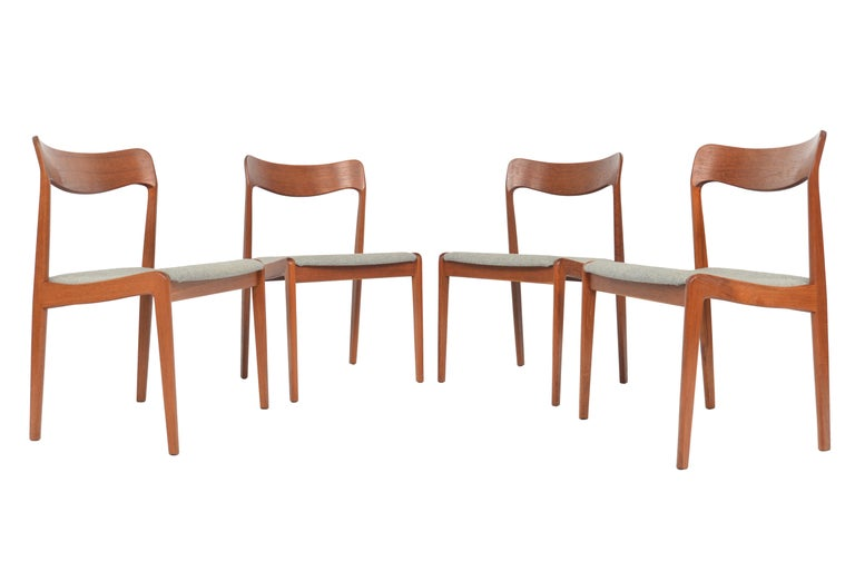 This set of four Danish modern dining chairs offer beautifully sculpted teak frames and nested seat bottoms. Seat bottoms are covered in grey Hallingdal wool. In excellent original condition.