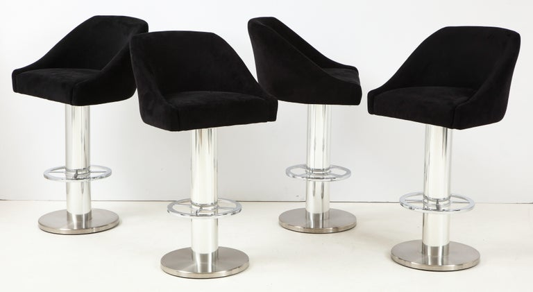 Set of four Design For Leisure barstools in chrome with original black Ultrasuede fabric. Well-made with heavy columnar chrome bases with footrests. Original label dated to 1997. In standout original condition with only minor wear consistent with