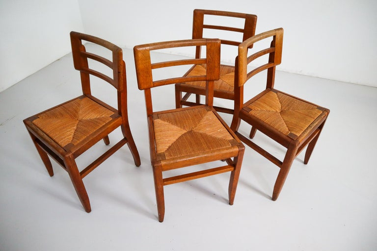 Modernist set of four chairs by designer Pierre Cruege made in France, 1940s. These models feature a sturdy backrest, consisting of wooden elements connected to each other by four slats. The seat is executed in woven cane. Works by French designer
