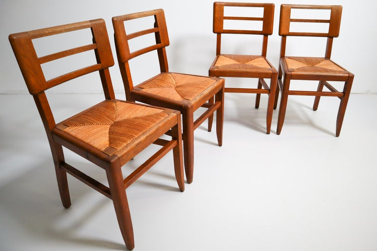 French Set of Four Dining Chairs by Pierre Cruege in Oak and Cane, France, 1940s For Sale