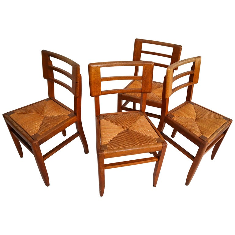 Set of Four Dining Chairs by Pierre Cruege in Oak and Cane, France, 1940s For Sale