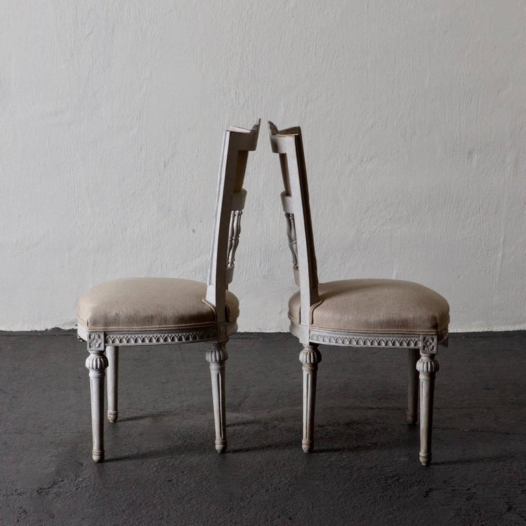 Dining chairs Set of four Swedish Gustavian 19th century white, Sweden. A set of four dining chairs made in Sweden during the Gustavian period. Frame in a white washed finish and decorated with leaf tip carvings and flowers. Legs rounded and