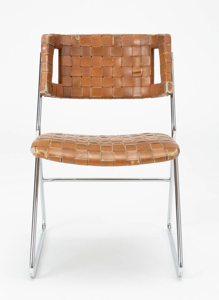 A set of four dining chairs from Missouri manufacturer Chromcraft. Designed in the 1970s, these sleek chairs have a sleigh base and narrow frame of chromed steel wire supporting a molded backrest and a seat cushion with rounded corners. Both back