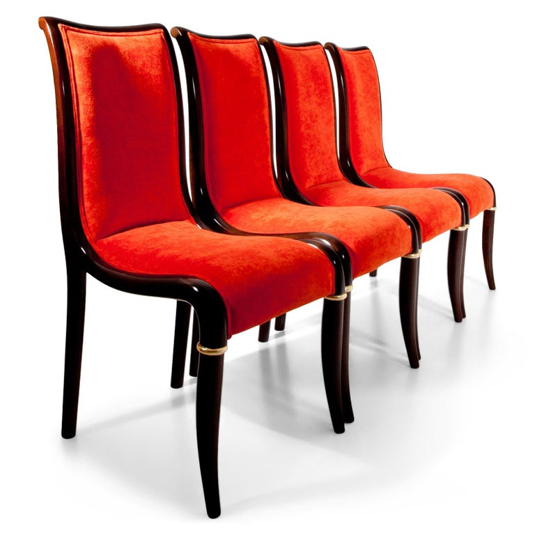 Four dining room chairs with elegantly curved backrests and seats. The front legs are accentuated with a gilt hoop. The chairs were reupholstered with a high quality orange fabric.