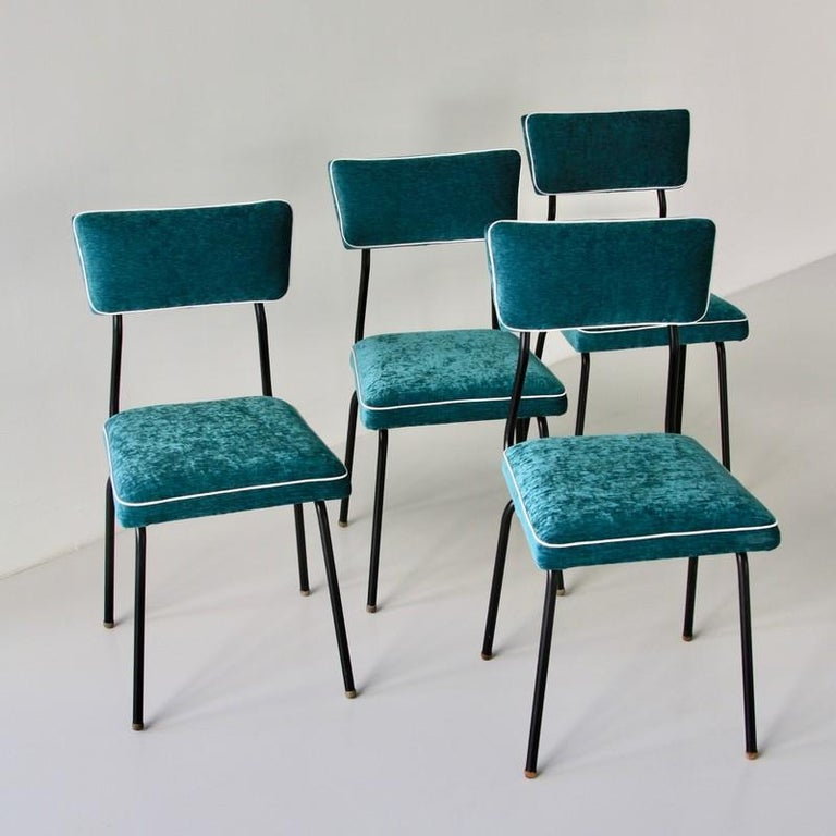 Set of four dining room chairs. France, 1950s.  Beautiful set of dining room chairs with metal frame painted in black, using round shaped wooden end pieces. Seat and back cushions upholstered in turquoise colored velvet with white borders. Seat