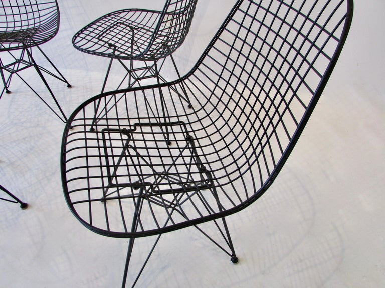 Charles and Ray Eames for Herman Miller DKR wire chairs on Eiffel tower bases. All four chairs have been refinished in a correct tone matte black powder coat. Three chairs have original style replacement glides one chair retains original glides. One