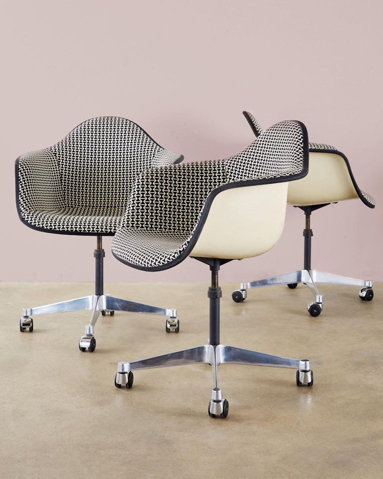 Dazzling mid-century set of four padded swivel chairs by Charles and Ray Eames for Herman Miller. The fiberglass shells are upholstered in a rare geometric black and white print with a black border. Supported by a four star polished swivel base