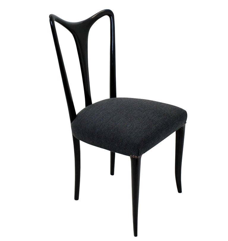 A set of four elegant dining chairs by Ulrich. Of finely tapering design in ebonized wood with newly upholstered grey seats.