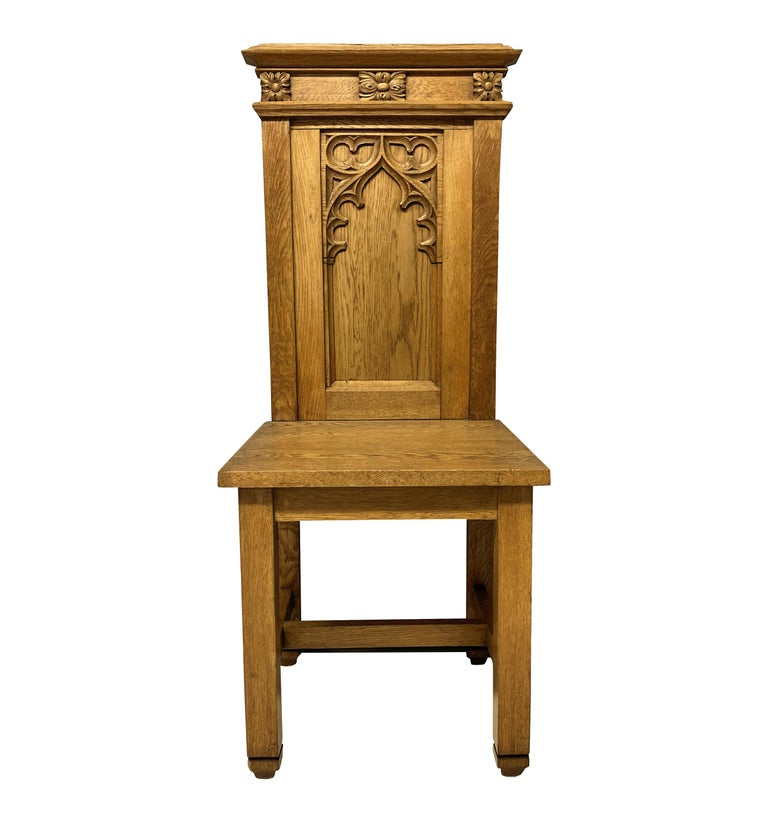 A set of four English pale oak Gothic hall chairs, with crisp carving.