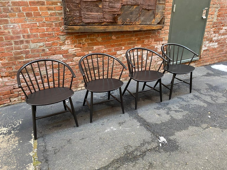 Set of four Ejvind A. Johansson designed spindle back chairs. Two are signed with the silver foil FDB Mobler, Danish control label. Good older restored black lacquer with some scratches and losses due to age and use. These elegant chairs feature a
