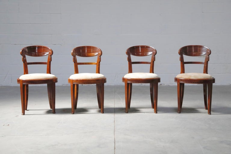 A superb suite of four French Art Deco Mahogany dining chairs with intricate wood detailing and suede upholstery, attributed to Sue et Mare, circa 1920s.   The deep luxurious mahogany frames have curved seat backs with carved scroll ends and faux