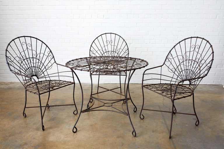 Distinctive set of four French Art Nouveau iron and wire patio garden chairs. The chairs feature a fan back or peacock style back design with wire work decorating the frames. Supported by legs ending with whimsical looped feet. Beautifully aged