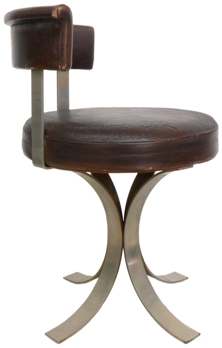 A fantastic and unusual set of four French midcentury dining chairs in leatherette and chromed steel. Wonderfully low-profile, playful-yet-graceful forms with an ample, disc seating area and correspondingly-arched backrest on footed pedestal-bases