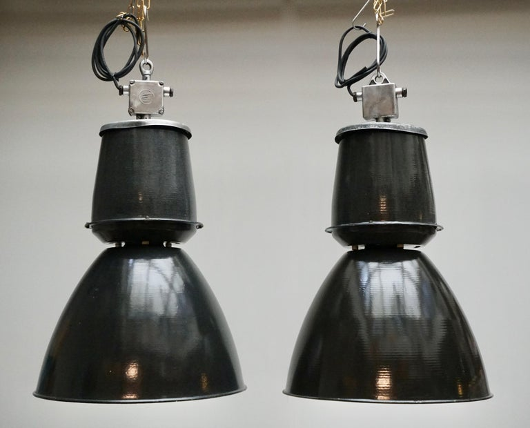 Eight Industrial down-lighters from the 1940s. Completely enameled inside and out. Greyish black on the outside, white on the inside. Great looking in a bar, a loft or over your kitchen table! Diameter:53 cm. Height:92 cm.