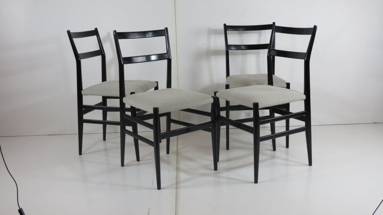 Four dining chairs designed by Gio Ponti and produced by F.gli Amedeo Cassina, 1952 provenience: Hotel in south Italy  laquered in black  newly reupholstered in grey cotton  very good original condition  ash and cotton  Measures: height: 83