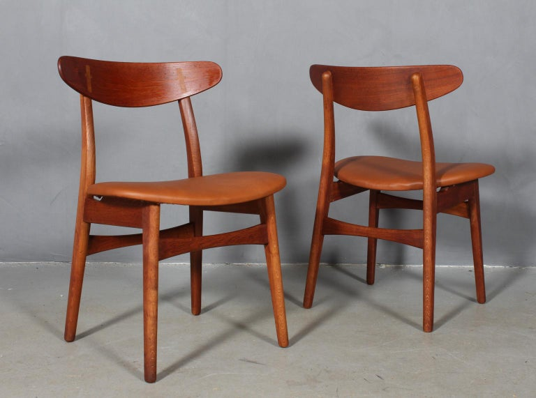Set of four Hans J. Wegner dining chairs in teak and oak.  New upholstered with walnut elegance aniline leather.  Made by Carl Hansen.   The CH-30 was originally designed in 1952 and was one of Wegner's first chairs. The design has become a