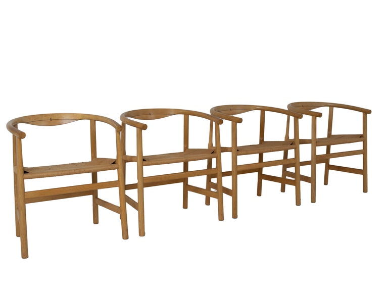 Amazing set of four armchairs designed by Hans Wegner and manufactured by PP Møbler, Denmark. These chairs are made of solid oak with wenge inlay. The seat is made of papercord. The design is timeless and very on-trend, for example in combination