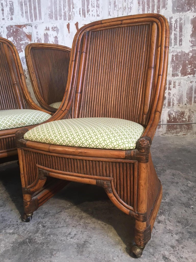 Set of 4 rattan dining chairs feature high back bamboo framework and caster wheels. Excellent vintage condition with very minor signs of age appropriate wear. Upholstery free of stains or wear.  Professional reupholstery available, ask for details.