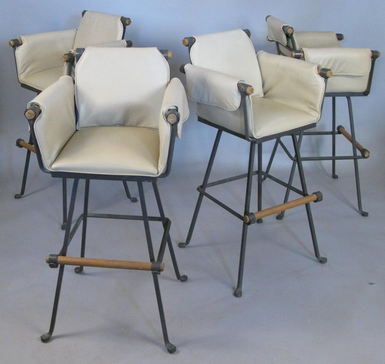 A beautiful set of four vintage 1970s swivel barstools with wrought iron frames and oak arms and footrests. With their original ivory vinyl upholstered seats and arms. Labelled terra furniture. Rare to find in a set this large and in very good