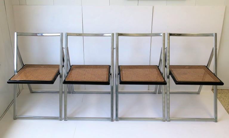 A beautiful and rare set of four (4) Italian Modern style or Postmodern period, chrome, black lacquered wood, and cane seat folding chairs, 20th century, circa 1970s, Italy. Marked