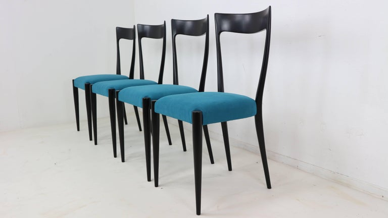 Set of four Italian modern dining chairs, designed by Melchiorre Bega, Italian, circa 1950s. These chairs are refinished and reupholstered in blue velvet.