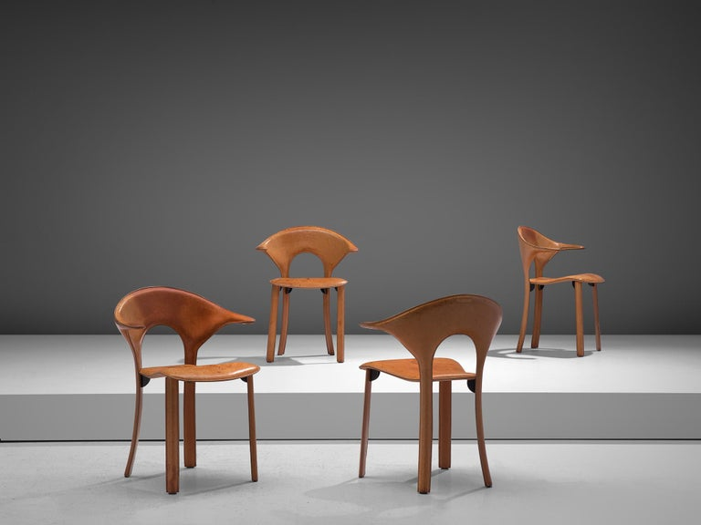 Set of four armchairs, attributed to Matteo Grassi, leather and metal, Italy, 1970s  These sculptural armchairs feature a completely leather surface with a rounded backrest and sculpted armrests. The leather is stitched and molded on to metal