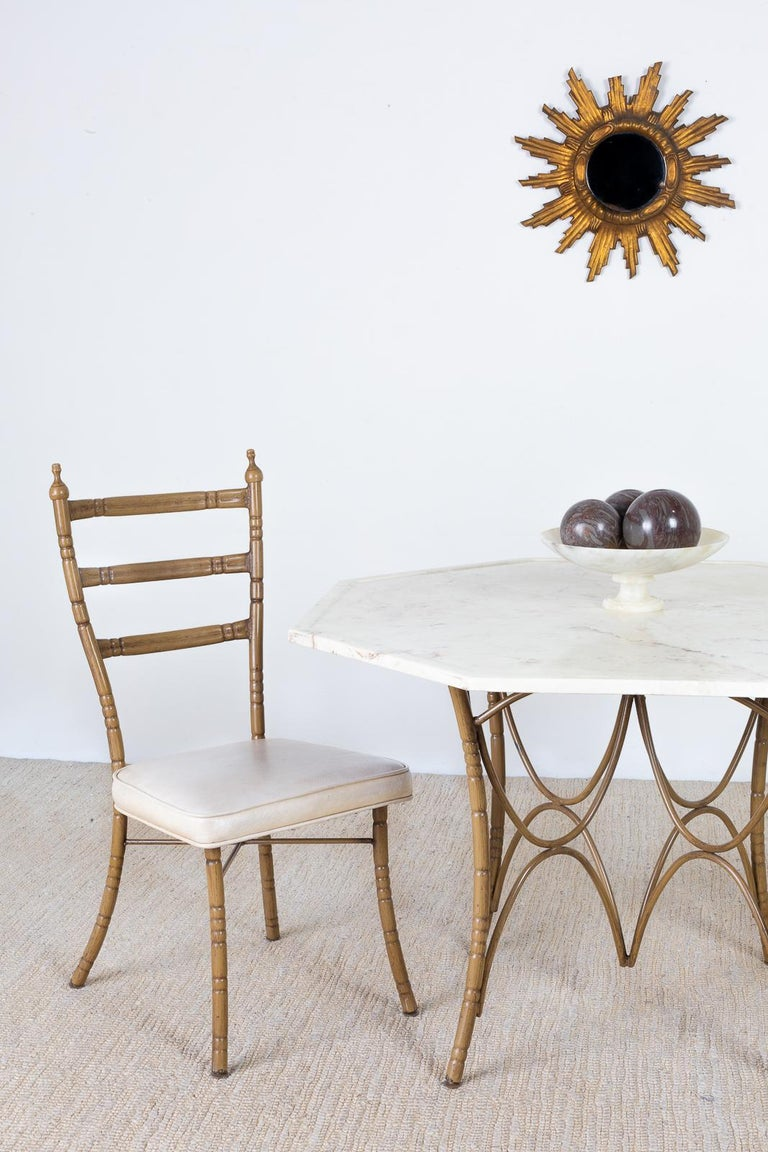 Whimsical set of four Italian Mid-Century Modern dining chairs featuring unique faux bamboo iron frames. Each chair has a ladder back design with splayed legs in the back. The chairs have graceful curves topped with a finial on each side. The iron