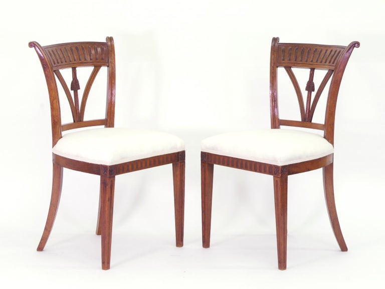 Set of four Italian solid ash side chairs, each with a fluted tablet over the spindle back with carved tassels; the upholstered seats on square tapered and fluted legs.  These delightful chairs have beautiful color and patina. Recently polished