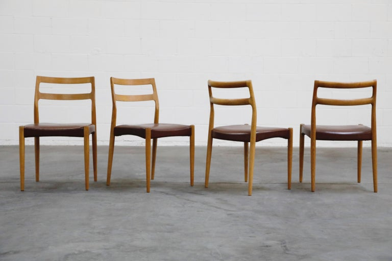 This lovely set of four (4) Danish Modern dining chairs are by Johannes Andersen for Uldum Møbelfabrik, sculpted from oak with leatherette upholstery, and in the style of Niels Otto Moller, these are a perfect option for interior designers and